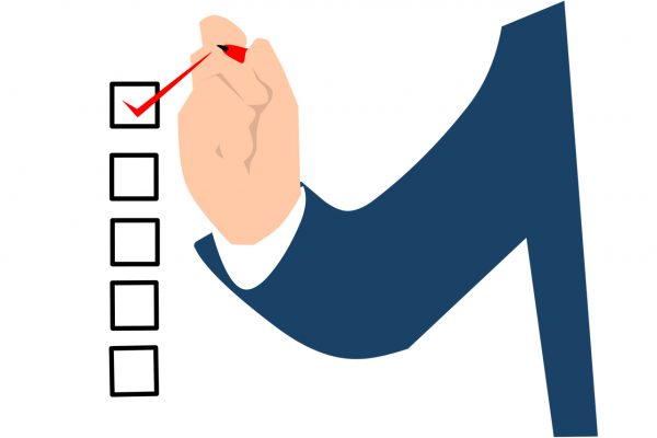 Hand with red pen ticking checklist boxes